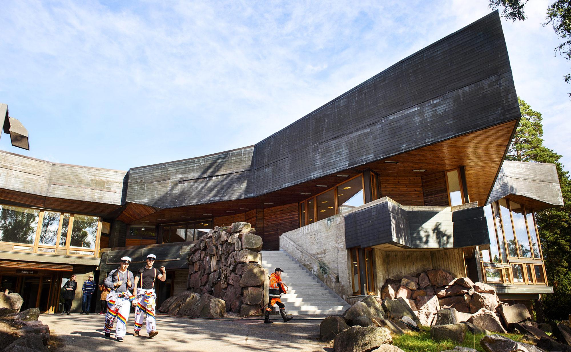 """Eteläiselle julkisivulle ovat luonteenomaisia voimakkaat räystäät. Reima Pietilän visiossa """"Dipolissa lahdekkeina leviävät ja vahvasti ulkonevat kupariräystäät ovat kallionkielekkeitä, joiden alle suojaan Luolamies rakentaa alkuasuntonsa."""""""