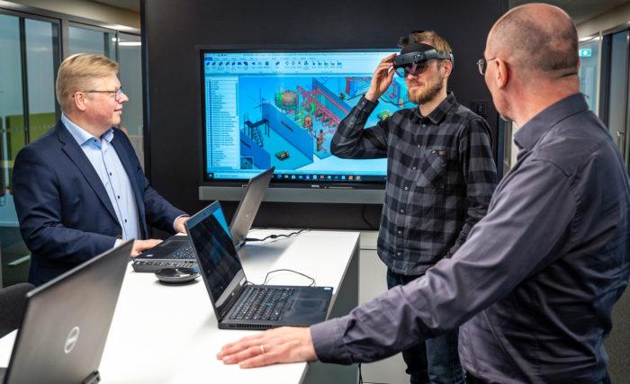 Cadmaticin toimitusjohtaja Jukka Rantala (vas.) ja Lead Software Architect Ilari Torsti (oik.) seuraavat, kun UX Director Teemu Valtonen käyttää Microsoftin HoloLens-laseja. Lasien avulla käyttäjä näkee Cadmaticin ohjelmistolla tehdyt 3D-suunnitelmat todellisessa ympäristössä.